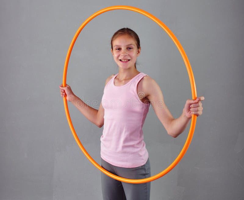 Den tonårs- sportive flickan gör övningar med hulabeslaget för att framkalla muskeln på grå bakgrund Ha gyckel som spelar leken S arkivfoto