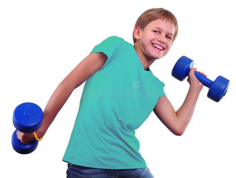 Den tonårs- sportive pojken gör övningar Sportig barndom Tonåring som övar och poserar med vikter Isolerat över vit backgr arkivbild