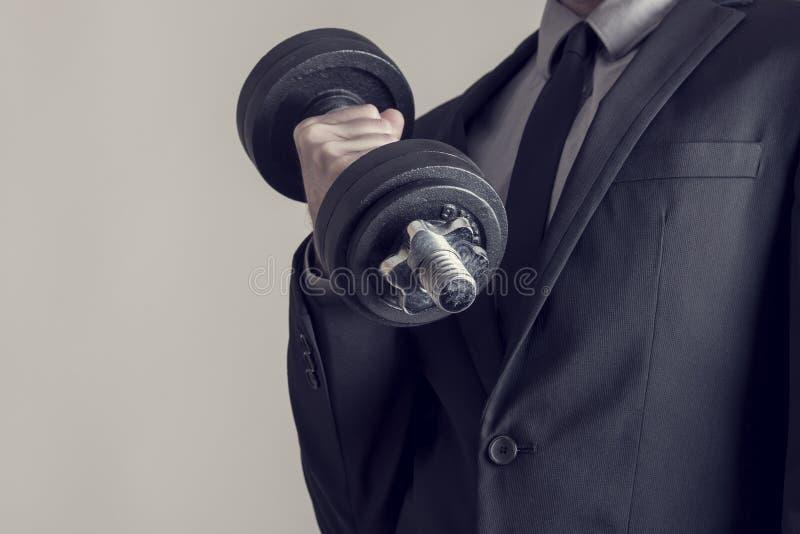 Den tonade bilden av en affärsman som gör hantelbiceps, krullar arkivbild