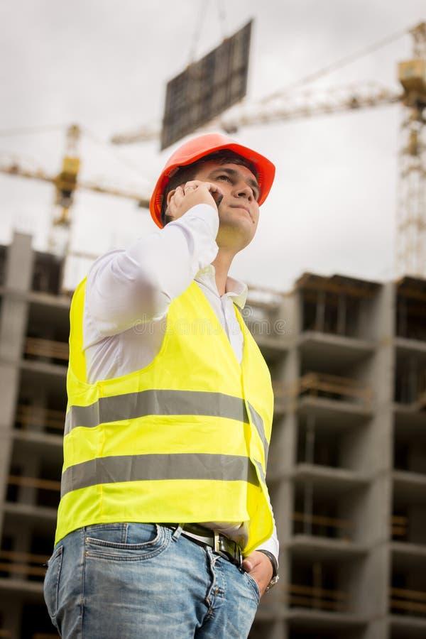 Den tonade ståenden av konstruktionsteknikern som talar vid telefonen lurar på royaltyfri bild