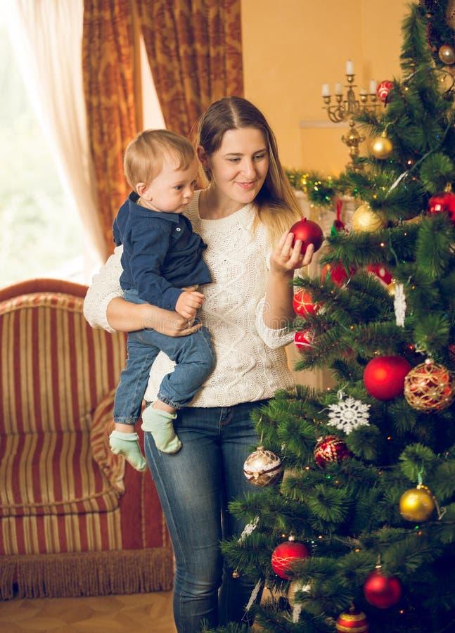 Den tonade ståenden av modern med 10 gamla månader behandla som ett barn att dekorera för son royaltyfri fotografi