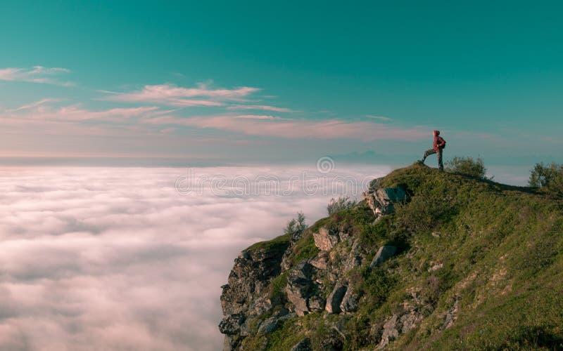 Den tonade vuxna kvinnan för bilden med en ryggsäck står på kanten av en klippa och att se soluppgången mot den blåa himlen royaltyfria foton