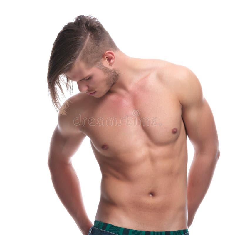 Den topless modemannen med händer i bac stoppa i fickan arkivfoto