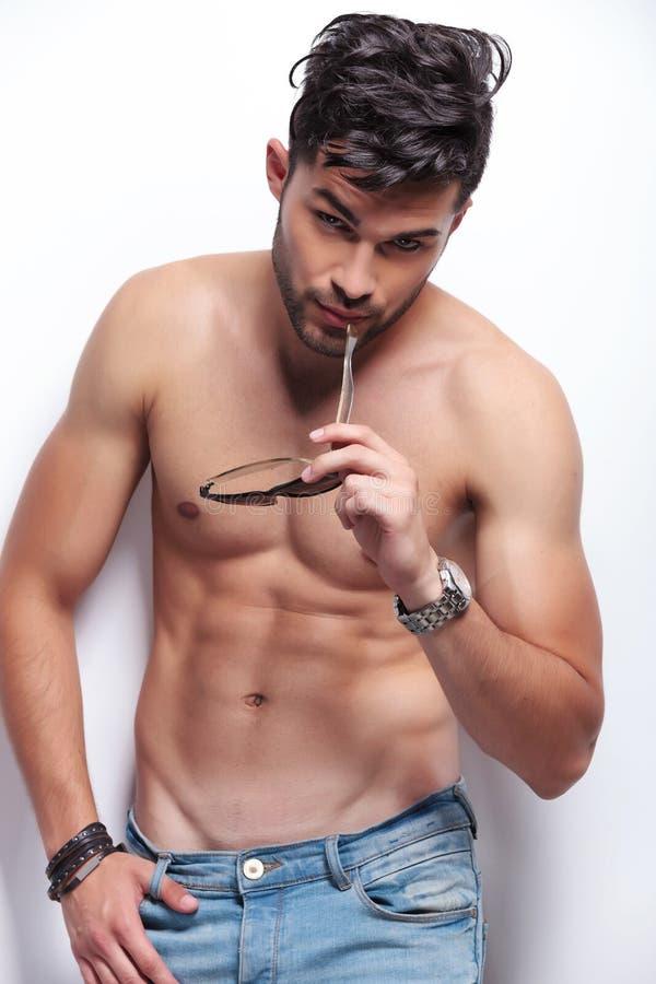 Den topless unga mannen biter hans solglasögon royaltyfria bilder