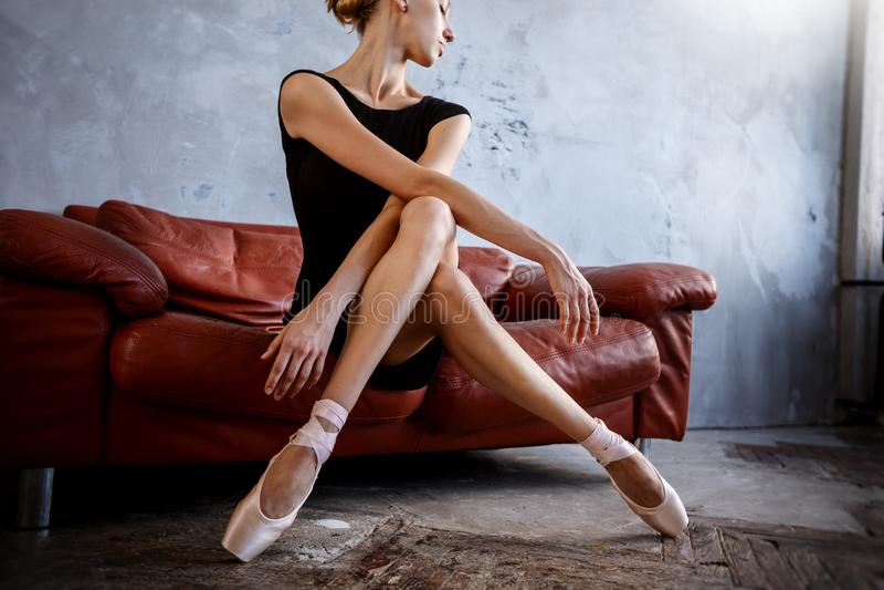 Den toppna slanka ballerina i en svart klänning poserar i studion arkivfoton