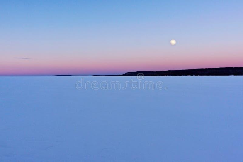 Den toppna snömånen av Februari visas över en djupfryst fjärd royaltyfri foto