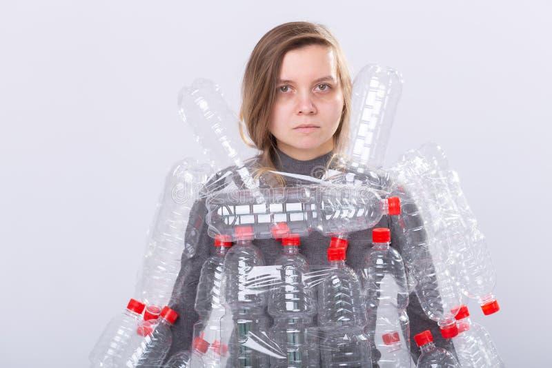 Den torkade sjuka kvinnan st?r med kl?nningen i plast- flaskor Milj?belastningproblem Stoppnaturavskr?de arkivbilder