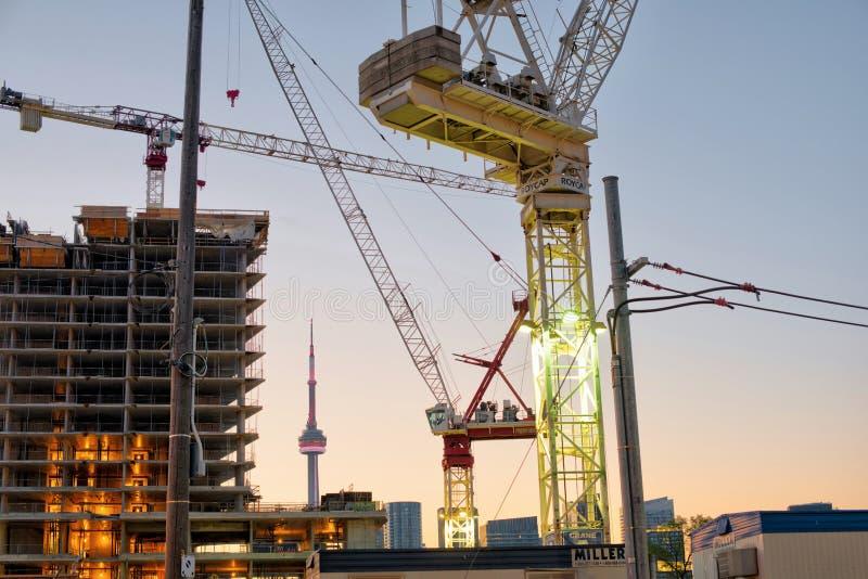 Den Toronto konstruktionsplatsen med kranar och CN står högt på soluppgång arkivbild
