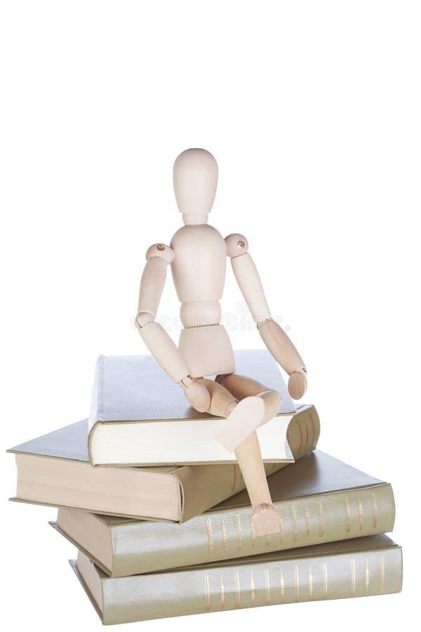 Den trälilla mannen sitter på böcker arkivfoto