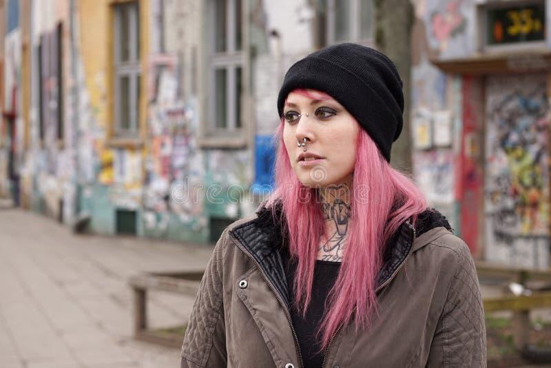 Den trängde igenom och tatuerade kvinnan av grafitti täckte framme byggnad arkivfoton