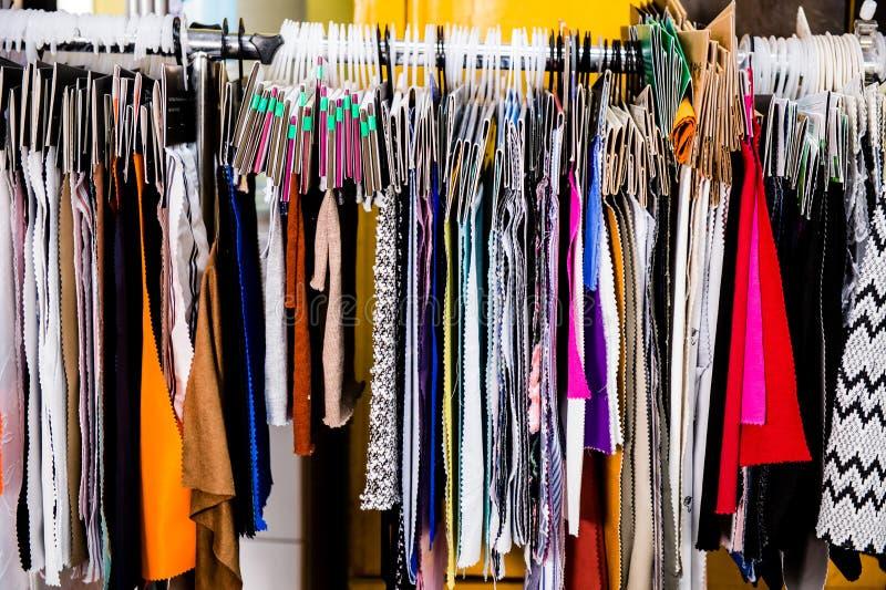 Den trängde ihop kuggen av kläder som hänger på hängare, belägger med metall lagerskärm från sidomodegarderoben arkivbilder