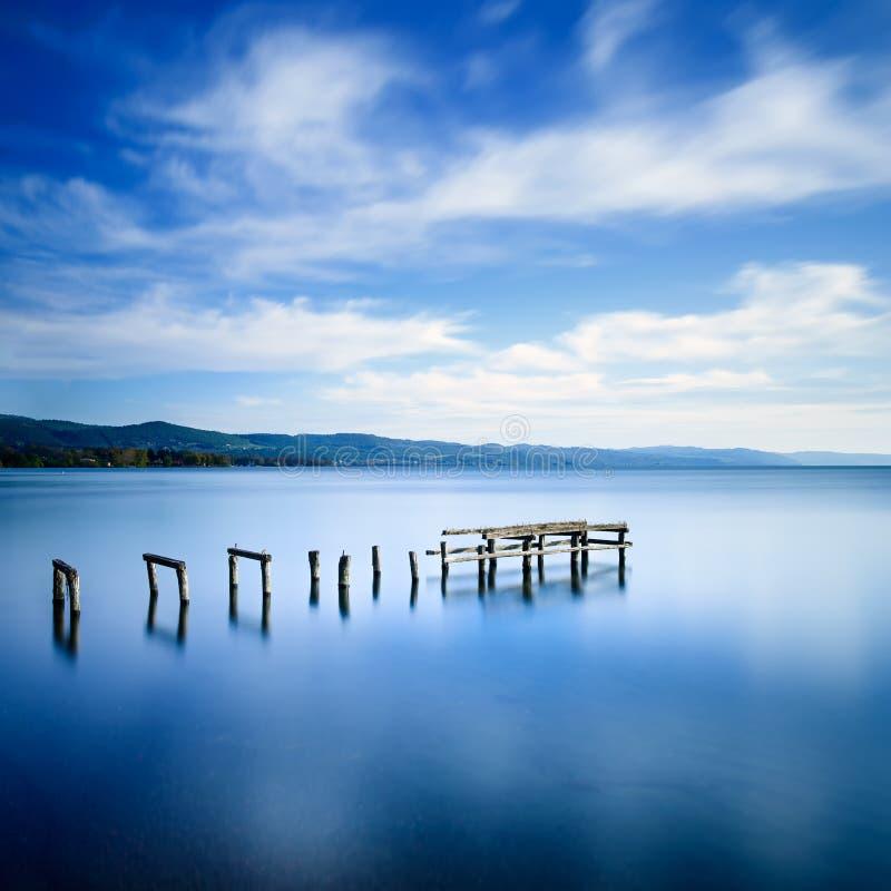 Den träpir eller bryggan återstår på en blå sjö. Lång exponering. royaltyfri bild