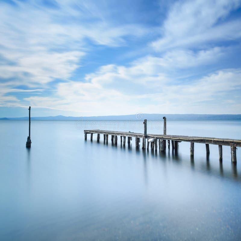 Den träpir eller bryggan återstår på en blå sjö. Lång exponering. royaltyfri foto