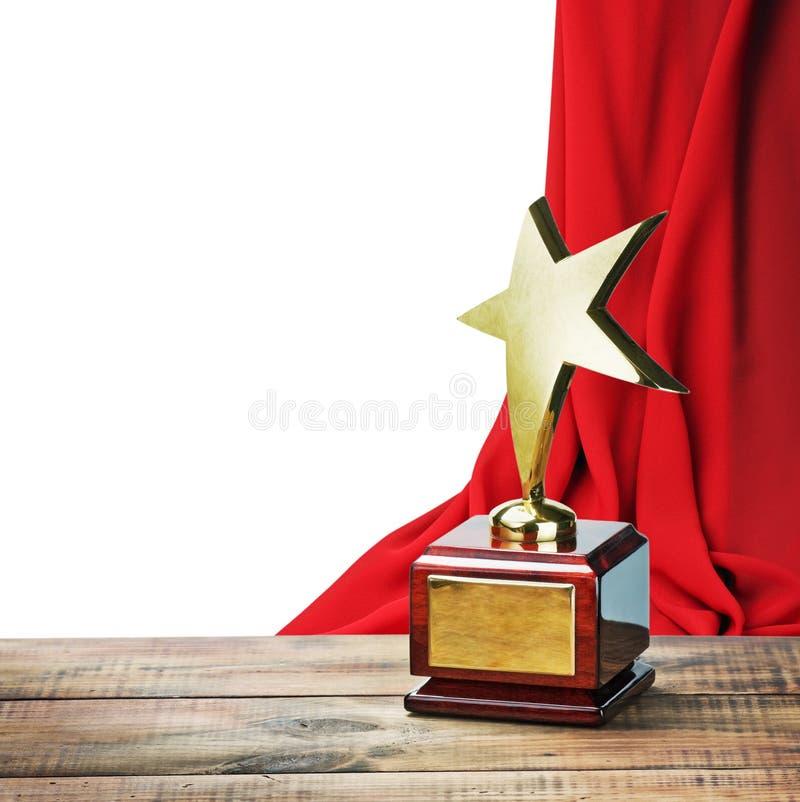 Den trästjärnautmärkelsen bordlägger och på bakgrunden av den röda gardinen arkivbild