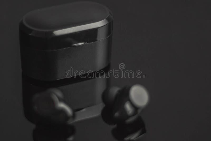 Den trådlösa hörlurar ligger på en svart bakgrundsnärbild royaltyfri bild