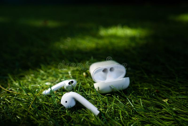 Den trådlösa hörlurar ligger på gräset, nära vinkel arkivfoto