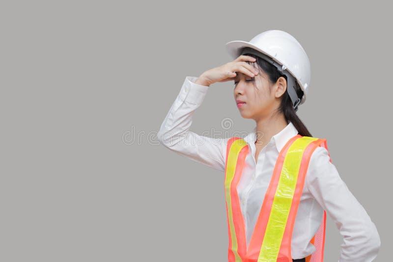 Den trötta överansträngde unga asiatiska kvinnaarbetaren som torkar svettats posera på grå färger, isolerade bakgrund arkivfoto