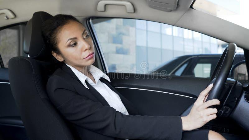 Den trötta förargade affärskvinnan klibbade i trafikstockning, sent för viktigt möte arkivbild