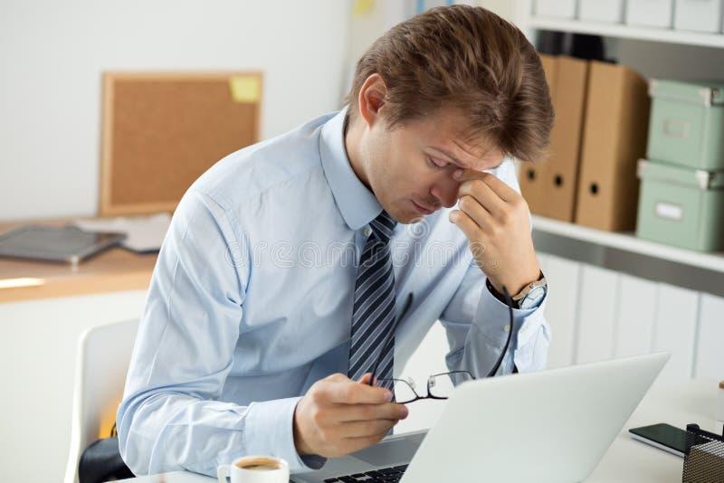 Den trötta kontorsarbetaren som trycker på hans bro av näsan för att ge sig, vilar till royaltyfri bild