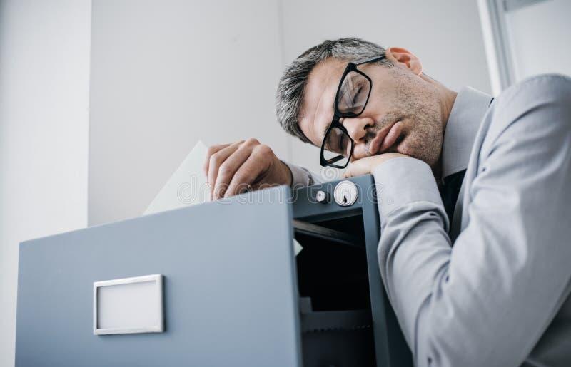 Den trötta lata kontorsarbetaren som lutar på en dokumentskåp och sover, faller han sovande stå upp; spänning unproductivity och royaltyfri bild