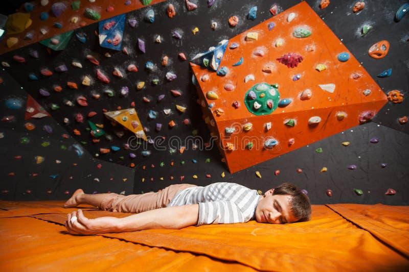 Den trötta manliga klättraren på det matta near vaggar väggen inomhus arkivbild