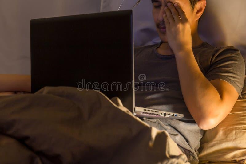 Den trötta mannen som på övertid arbetar i säng på natten med handen, gnider hans ögon arkivfoto