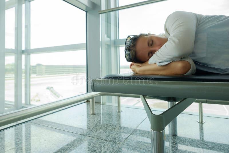 Den trötta passageraren sover nolla i flygplatsterminal och väntande på flygplanankomst royaltyfri fotografi