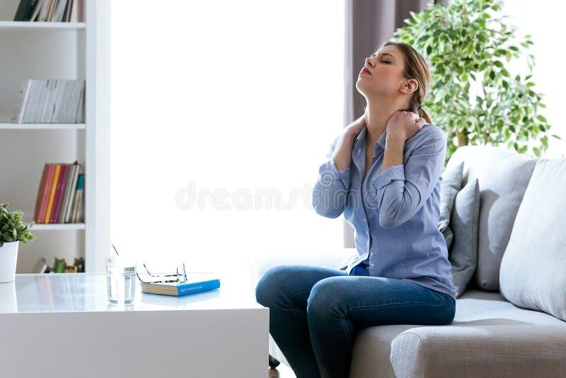 Den trötta unga kvinnan med halsen smärtar sammanträde på soffan hemma arkivbilder