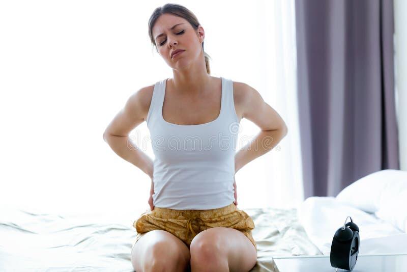 Den trötta unga kvinnan med tillbaka smärtar sammanträde på sängen hemma arkivbilder