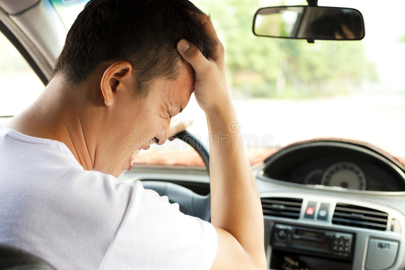 Den trötta unga mannen har en huvudvärk, medan köra bilen arkivfoto
