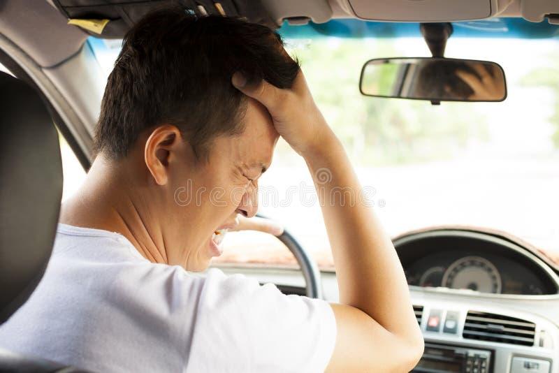 Den trötta unga mannen har en huvudvärk, medan köra bilen arkivfoton