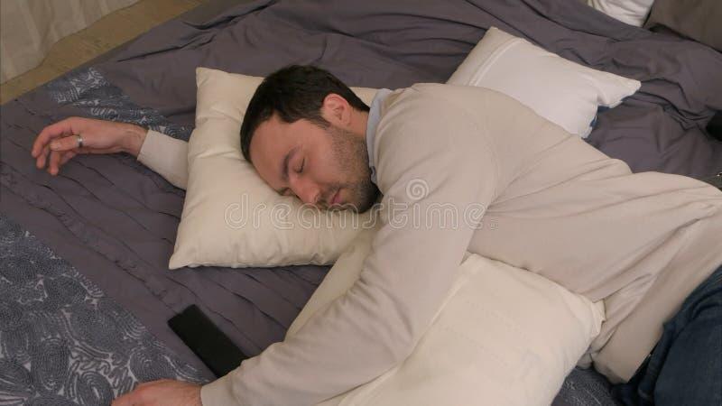 Den trötta unga mannen ligger på säng och faller sovande efter hård arbetsdag arkivfoto