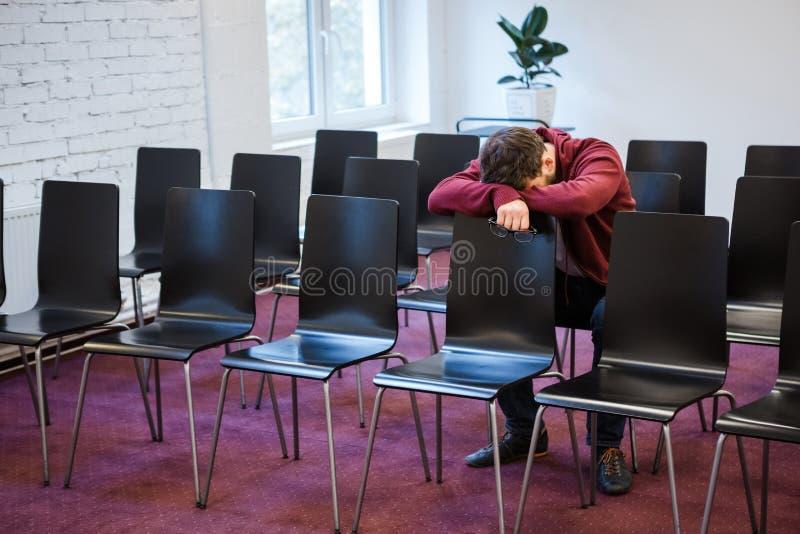 Den trötta unga mannen ta sig en lur i konferensrum royaltyfria foton