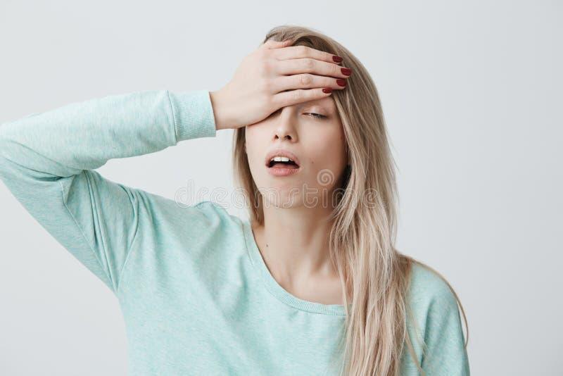 Den trötta utmattade blonda unga kvinnlign har ruskig huvudvärk efter arbete, kommer hem i dåligt lynne, matas upp med royaltyfri foto