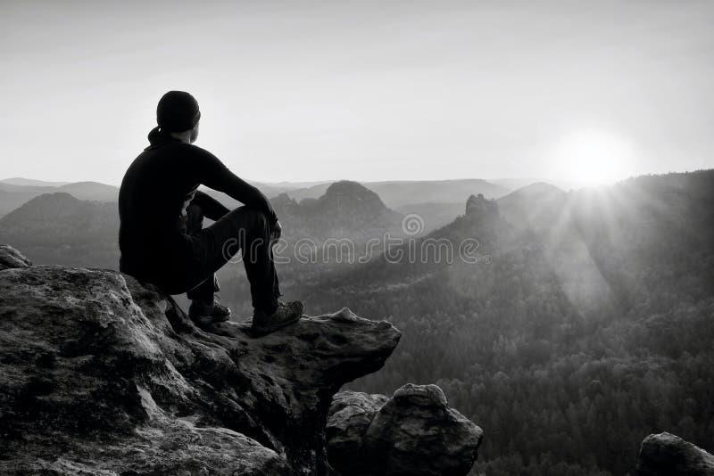 Den trötta vuxna fotvandraren i svart byxa, omslaget och mörkerlocket sitter på klippkanten och att se till färgrik mist i dalbrö royaltyfri fotografi