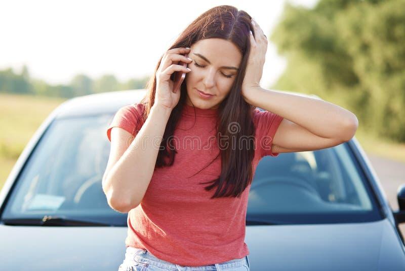 Den tröttade europeiska kvinnan med långt hår har telefonkonversation via mobiltelefonen, känner sig trött, når han har reparerat royaltyfri fotografi