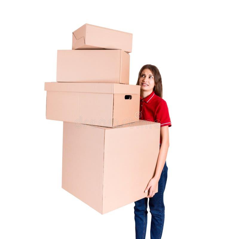 Den tröttade leveranskvinnan rymmer en bunt av tunga kartonger Den nätta flickan evakueras efter hård dag som isoleras på vit royaltyfria foton