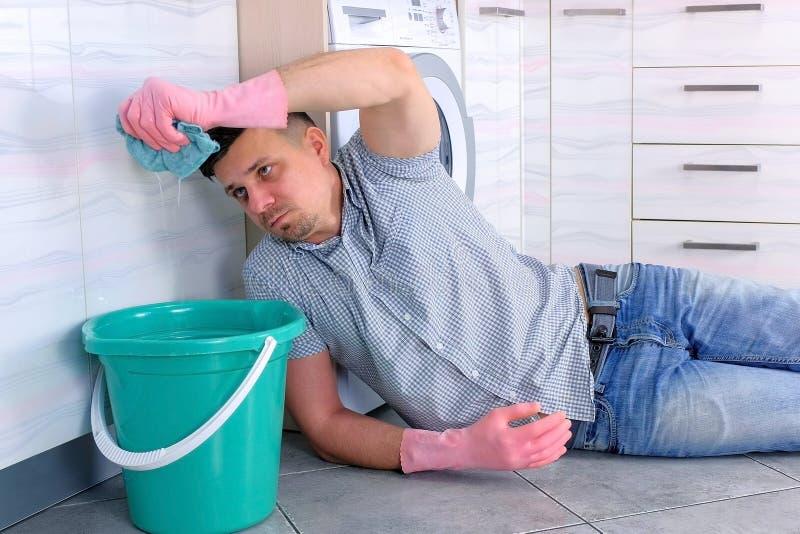Den tröttade mannen i gummihandskar trycker på trasan över hinken som lägger på kökgolvet fotografering för bildbyråer