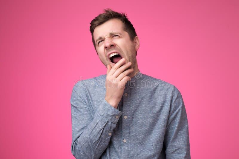 Den tr?ttade mannen k?nner sig s?mnig, g?spar som k?nner sig tr?tt, ?ppnar munnen brett, poserar ?ver rosa bakgrund arkivfoto
