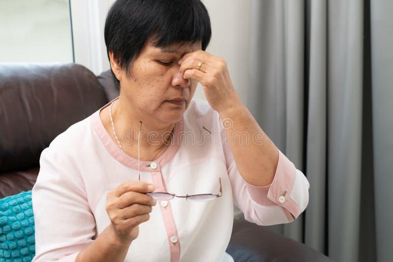 Den tr?tta gamla kvinnan som tar bort glas?gon som masserar synar, n?r han har l?st den pappers- boken k?nsligt obehag p? grund a royaltyfri foto