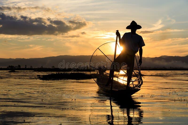 Den traditionella Burmese fiskaren på Inle sjön, Myanmar som var berömd för deras särskiljande, lade benen på ryggen ro stil fotografering för bildbyråer