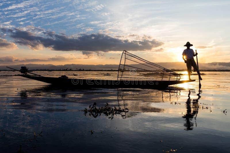 Den traditionella Burmese fiskaren på Inle sjön, Myanmar som var berömd för deras särskiljande, lade benen på ryggen ro stil arkivfoto