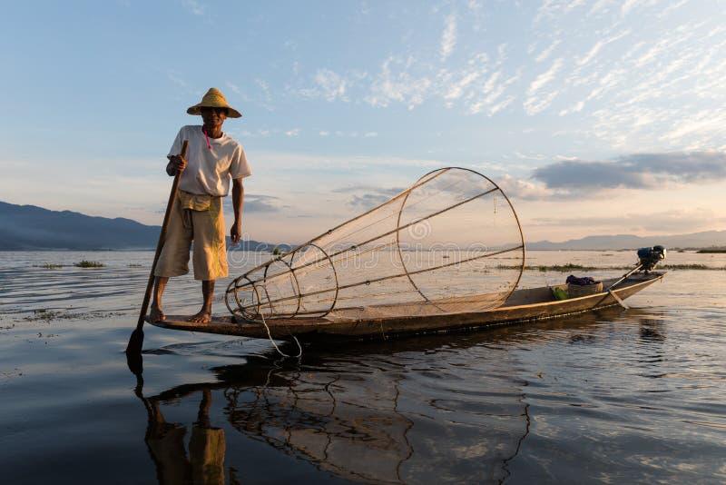 Den traditionella Burmese fiskaren på Inle sjön, Myanmar som var berömd för deras särskiljande, lade benen på ryggen ro stil royaltyfria foton