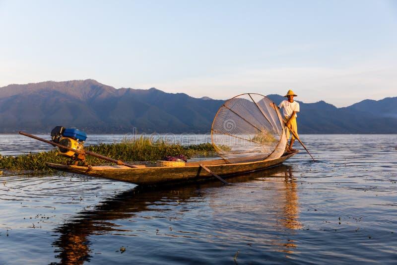 Den traditionella Burmese fiskaren på Inle sjön, Myanmar som var berömd för deras särskiljande, lade benen på ryggen ro stil arkivbilder