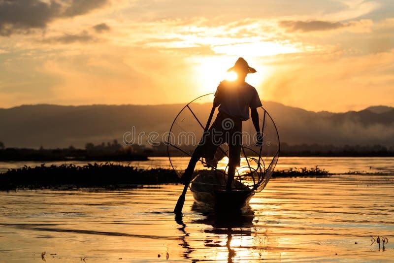 Den traditionella Burmese fiskaren på Inle sjön, Myanmar som var berömd för deras särskiljande, lade benen på ryggen ro stil royaltyfri fotografi