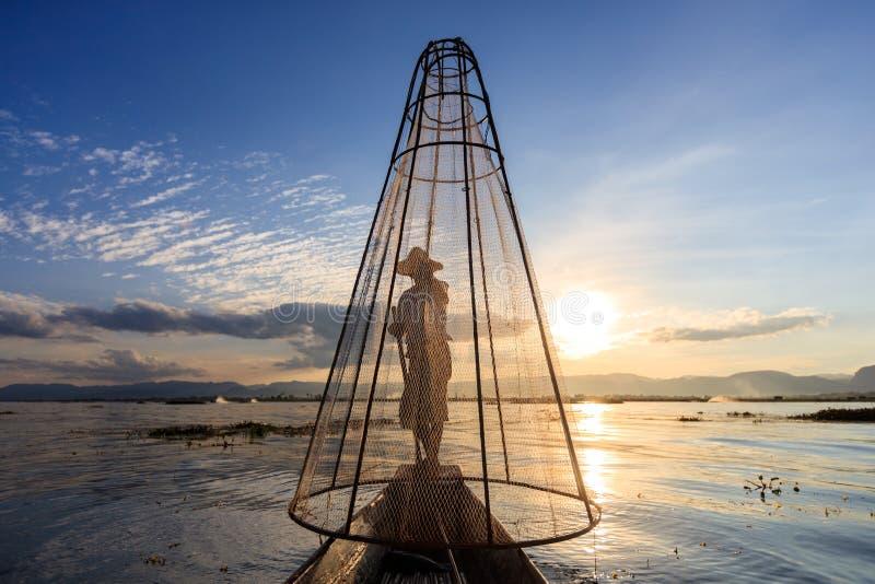 Den traditionella Burmese fiskaren på Inle sjön, Myanmar som var berömd för deras särskiljande, lade benen på ryggen ro stil arkivfoton