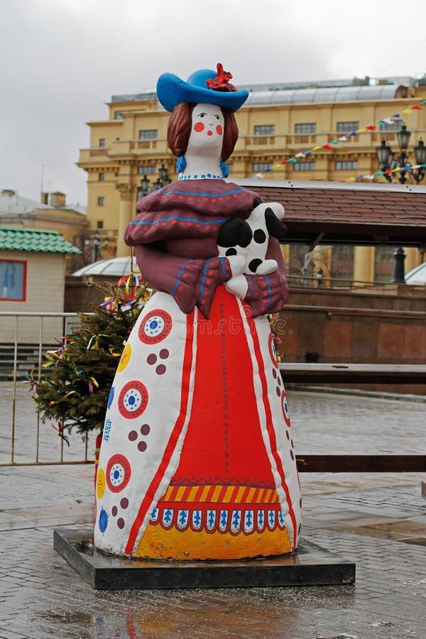 Den traditionella Dymkovo leksakkvinnan med hunden som konstobjekt på rysk nationell festival` Shrove ` på den Manezhnaya fyrkant royaltyfri fotografi