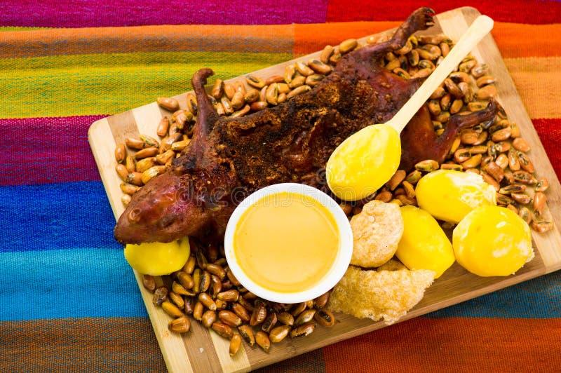 Den traditionella ecuadorianmaträtten, den grillade försökskaninen fördelade ut på träbräde, tostados, baconhud och citroner på royaltyfri bild