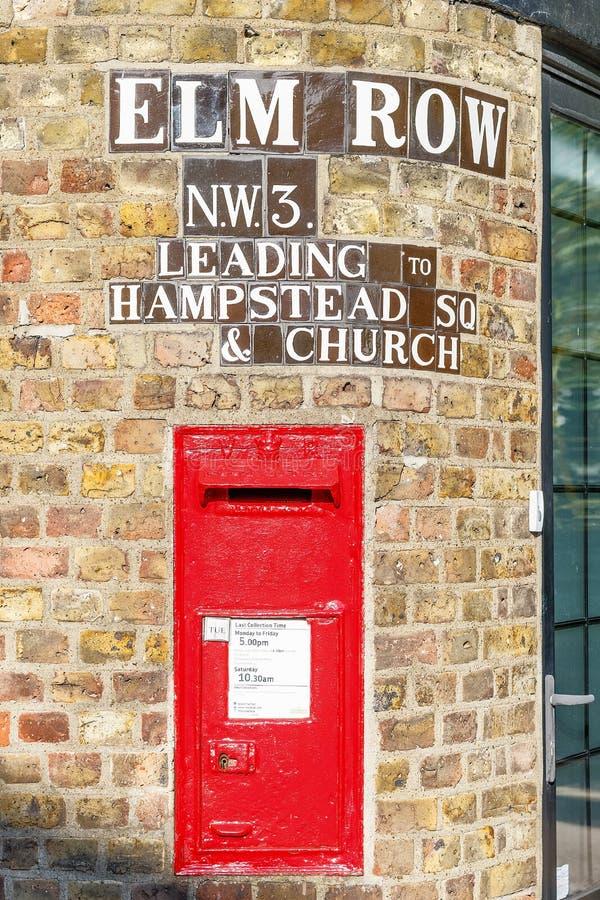 Den traditionella gamla engelska röda postboxen monterade i en randvägg arkivfoton