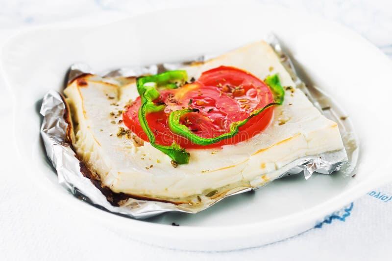 Den traditionella grekiska ugnen bakade fetaost med örter och veggies arkivfoton